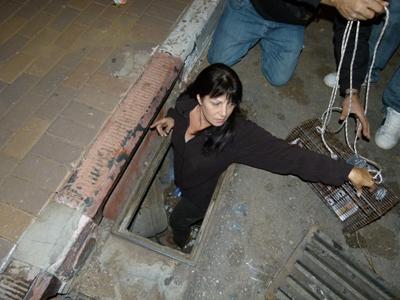 רונית מהעמותה מצילה גור ממרזב בכביש
